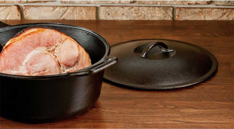 A traditional bare cast iron dutch oven with lid from Lodge Manufacturing.