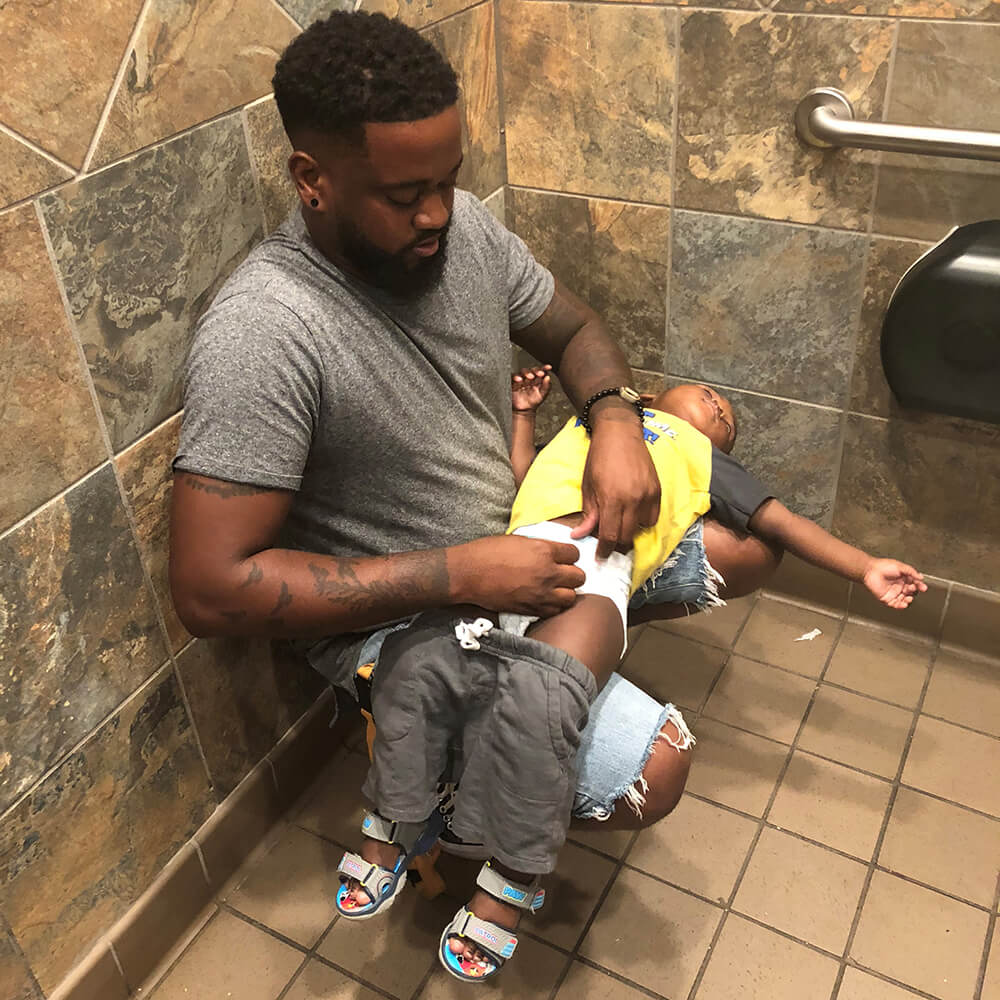Donte Palmer changing son's diaper without a changing station