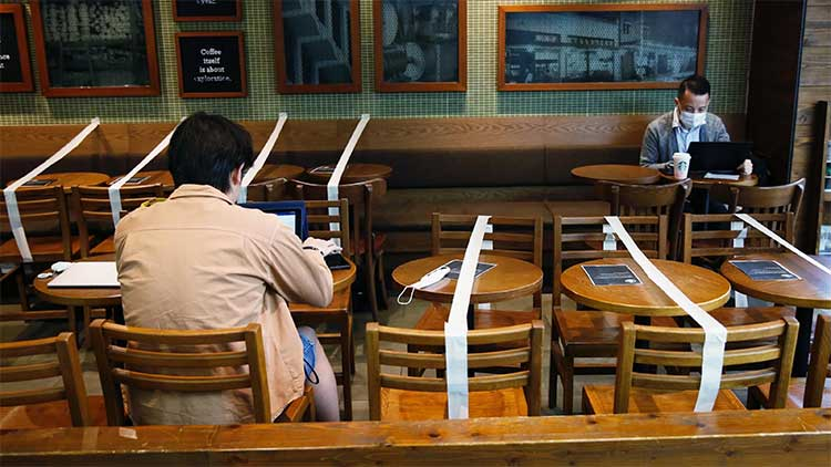 Using masking tape to block off table to enforce social distancing can work, but you might want to consider other options that are more professional-looking. (Reuters - Tyrone Siu)