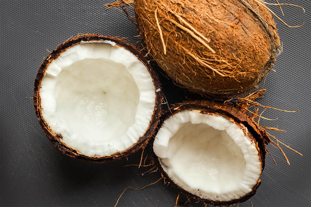 Pair of coconuts with one cut in half showing what makes coconut milk, a dairy alternative.