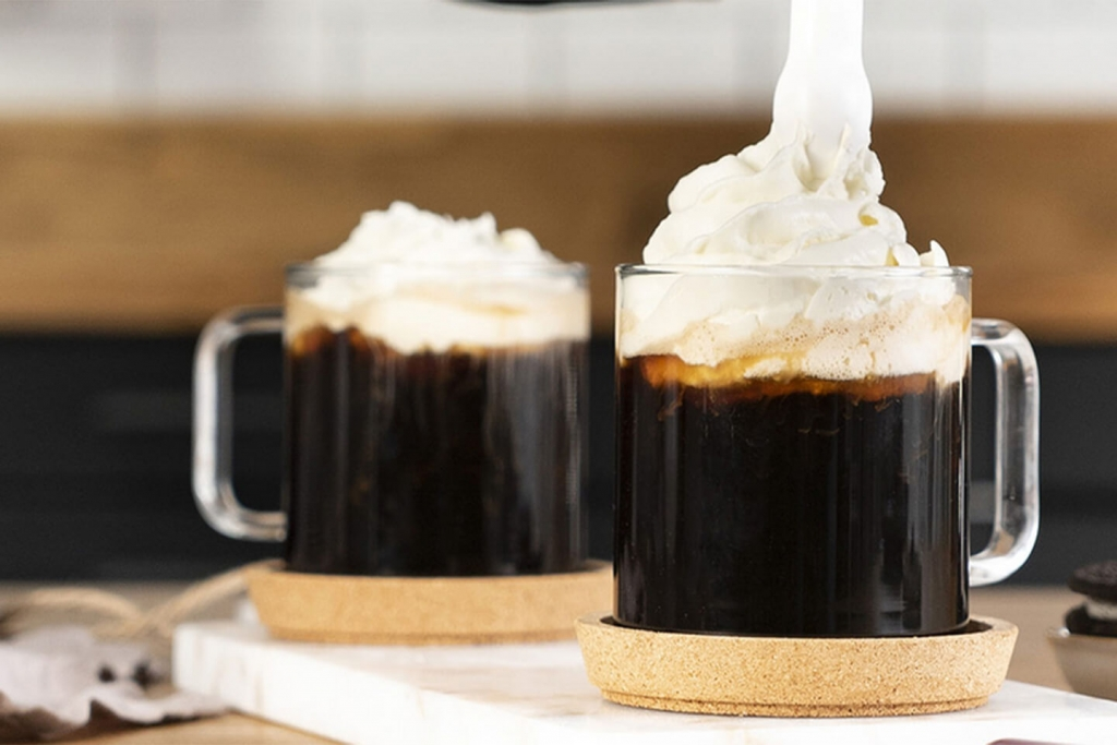Whipped cream in a coffee beverage created from iSi whipping siphon.