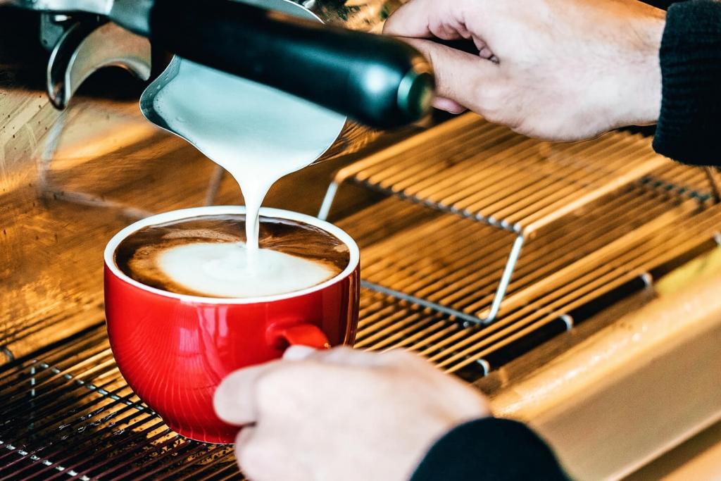 Barista adding milk to an espresso beverage.