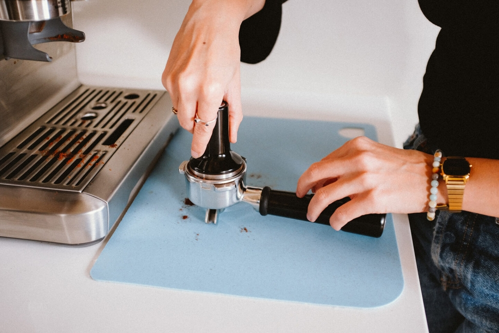 Barista tamps the grounds.